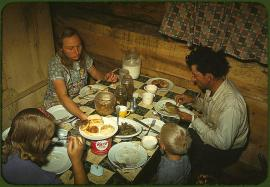 The Faro Caudill family eating dinner in their dugout. Pie Town, New Mexico, October 1940. Reproduction from color slide. Photo by Russell Lee. Prints and Photographs Division, Library of Congress